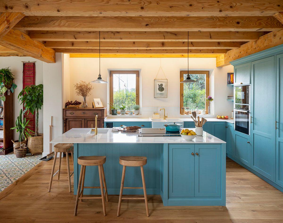 Zona de bucătărie este evidențiată atât prin mobilierul specific, cât și prin arhitectura spațiului. Deasupra bucătăriei plafonul este mai jos, iar lemnul prezent pe două suprafețe paralele: pardoseală și bârne din lemn de la nivelul plafonului. Între ele zugrăveală albă, iar pe acest fundal designerul a venit cu o nuanță de mobilier în contrast cu auriul lemnului, dar a prevăzut blaturile la fel ca pereții: albe.
