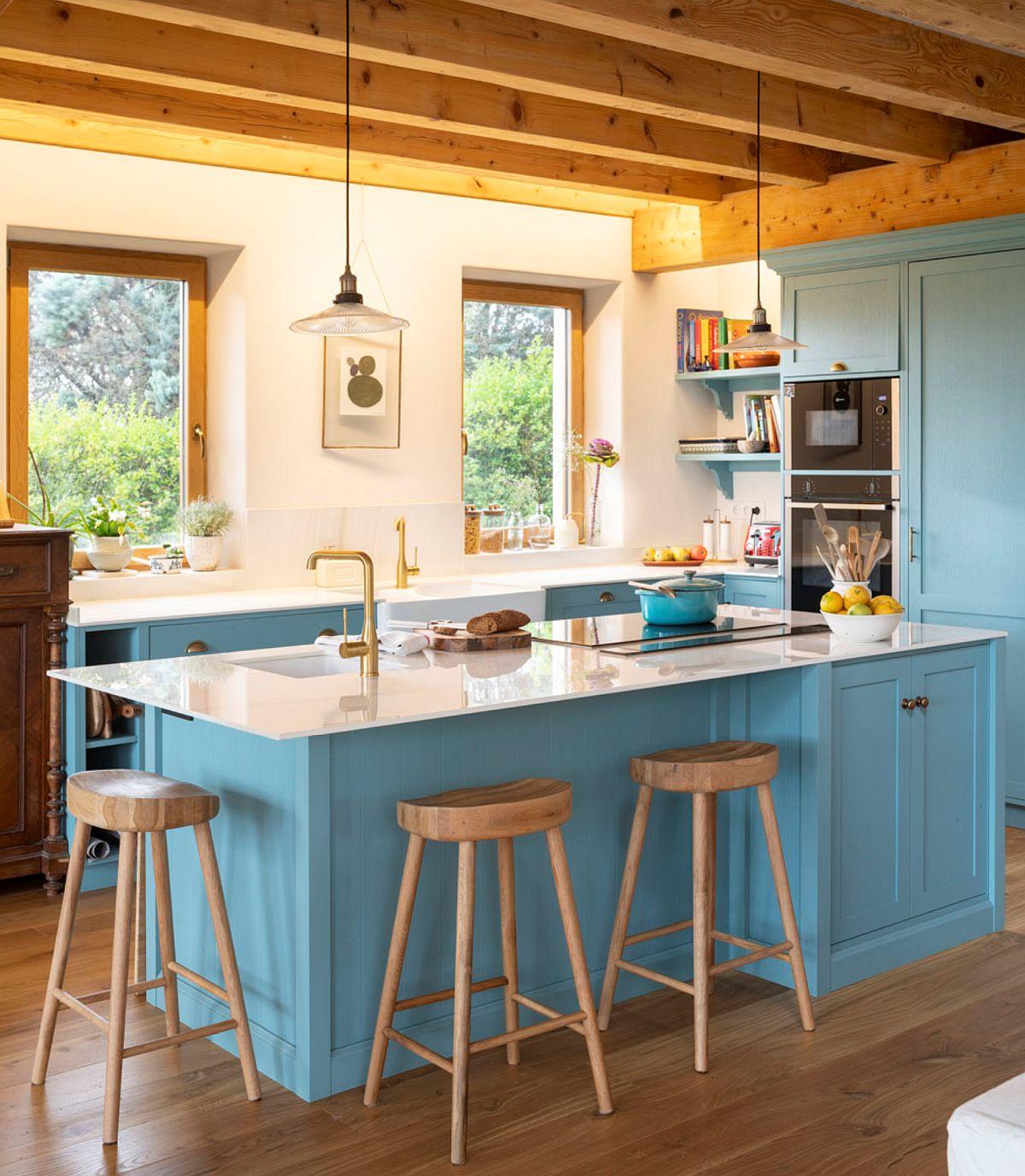 Rustic și actual sunt frumos împretite în cazul bucătăriei, unde designerul a prevăzut blaturi subțiri, contemporane în relație cu un mobilier din MDF care are desen rustic.