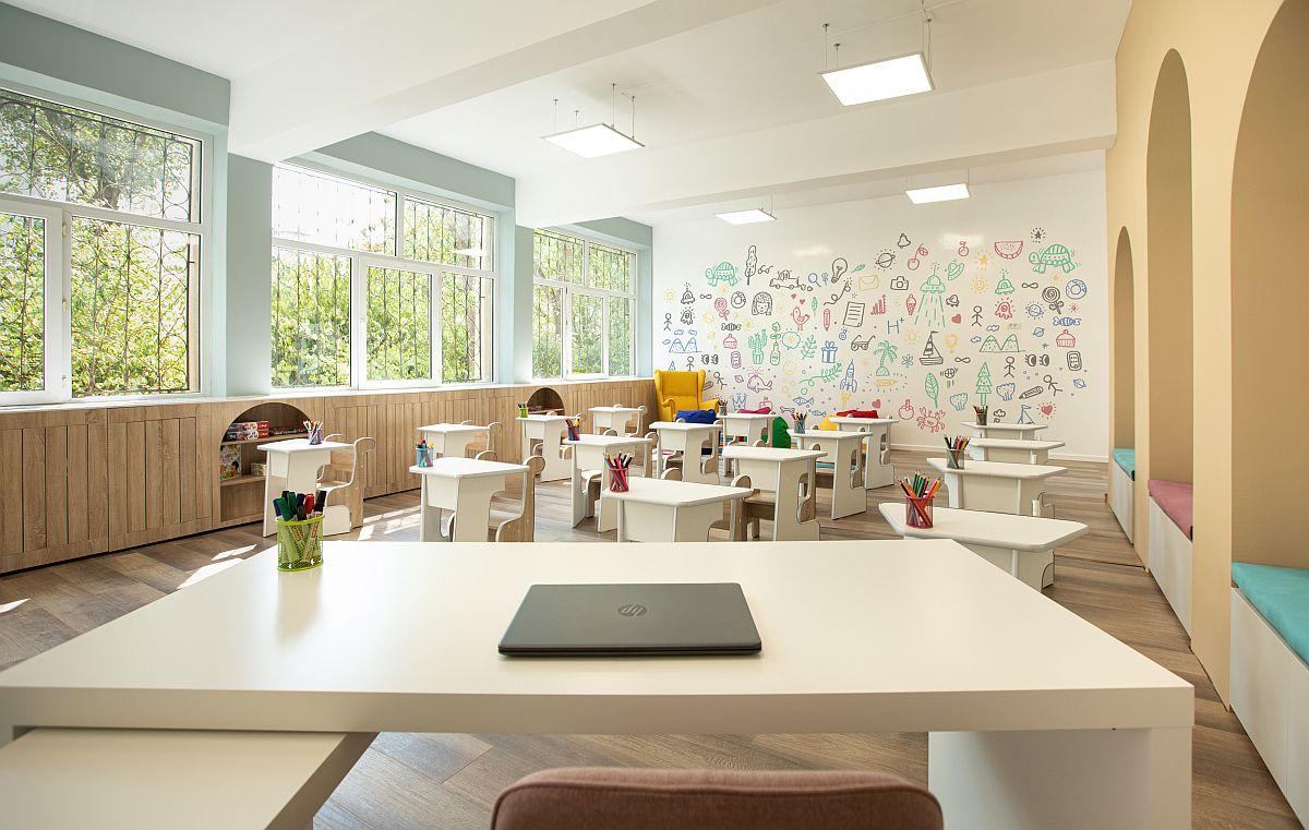 Catedra este orientată pe un colț pentru ca locul învățătoarei să fie perceput ca fiind mai prietenos și impunător pe mijlocul spațiului. Doi dintre pereții clasei sunt finisați cu vopsea cu efect de tablă, astfel că suprafața lor poate deveni și loc de joacă, de decorare, nu doar pentru învățare.