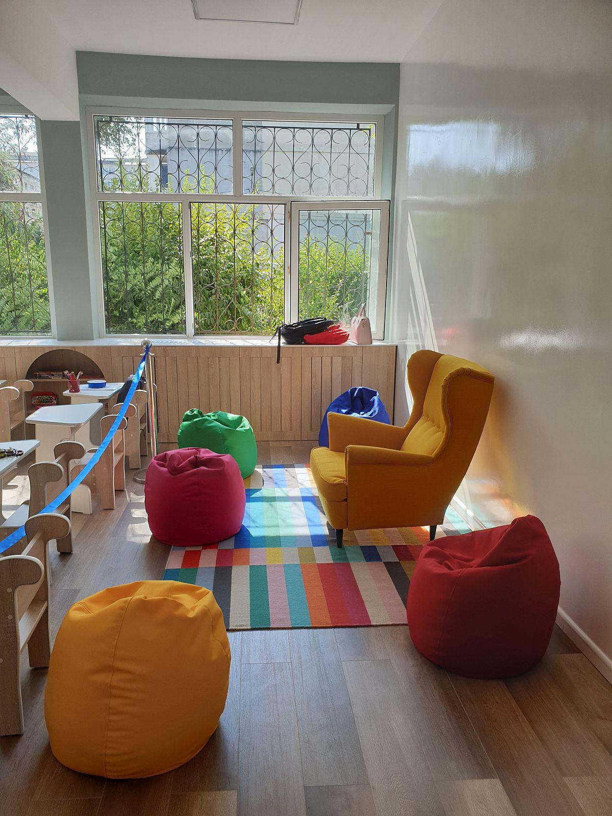 La intrarea în clasă, prima zonă care se vede este cea de lectură. Copii pot sta pe covor și pe pufuri pentru a asculta poveștile citite de către doamna învățătoare.