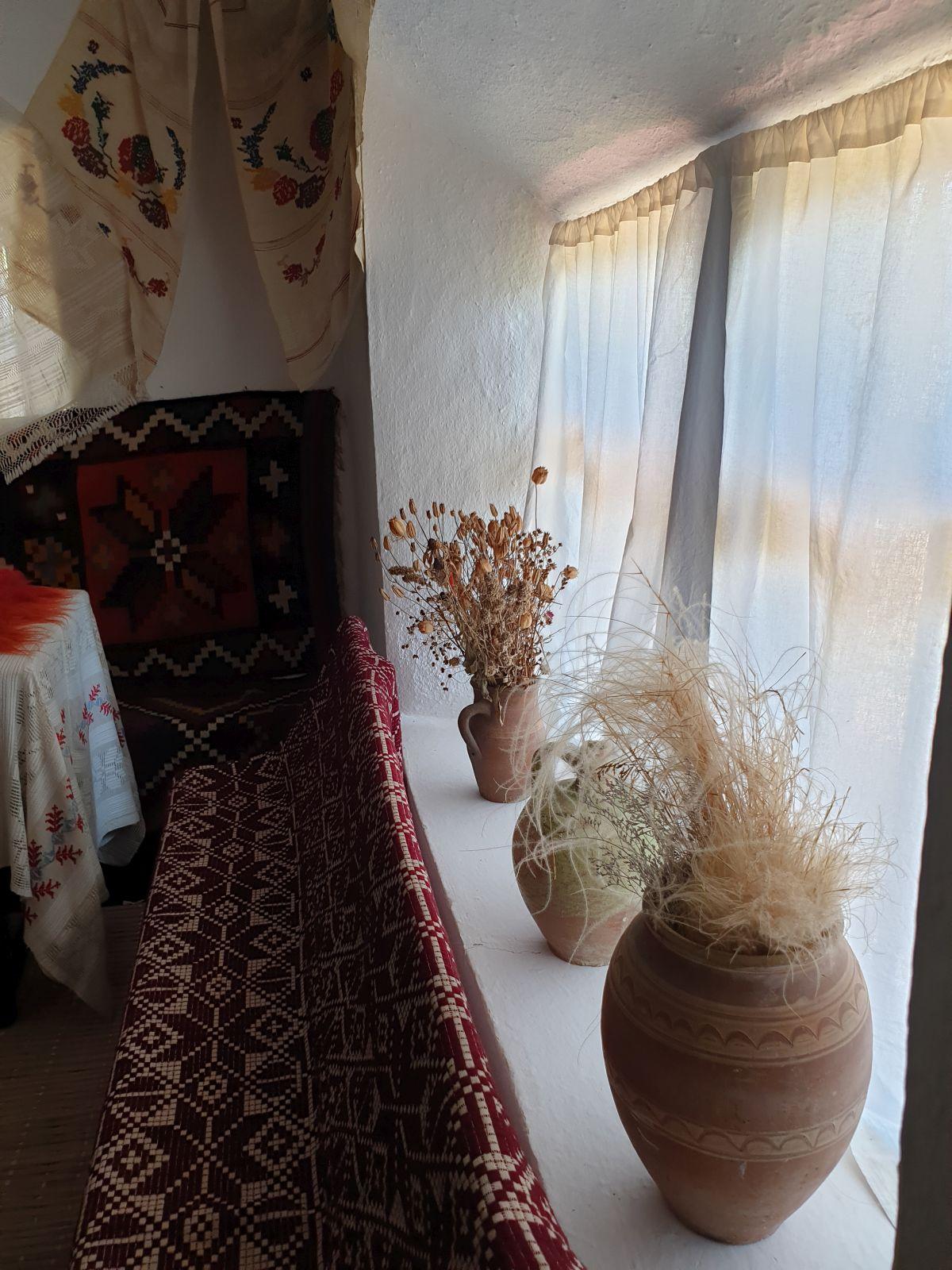 Plante specifice zonei, uscate și puse în vase de ceramică. decorează locul ferestrelor alături de țesăturile tradiționale.