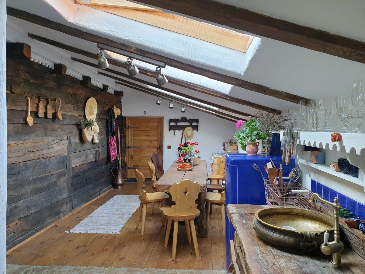 Intrarea în magazie a devenit acum intrarea casei folosită în mod curent. Peretele exterior al casei din lemn se simte acum ca un finisaj interior texturat, spațiul nou construit fiind tot din lemn, dar la interior tencuit.
